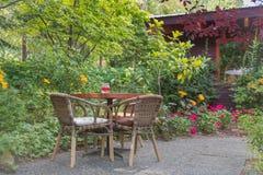 Tabela e cadeiras no restaurante do jardim do pátio no verão imagem de stock