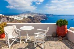 Tabela e cadeiras no telhado com uma opinião do panorama na ilha de Santorini, Grécia fotografia de stock royalty free