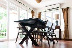 Tabela e cadeiras pretas na sala de visitas Foto de Stock