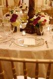 Tabela e flores do copo de água Fotos de Stock Royalty Free