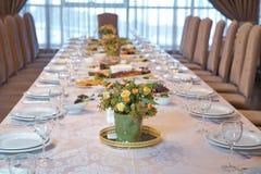 Tabela elegante ajustada com os vidros decorados no ouro, iluminados velas e flores vermelhas imagem de stock