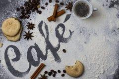 Tabela escura decorada com o café da palavra feito da farinha de trigo fotografada de cima para baixo, mais um copo pequeno do ca imagens de stock