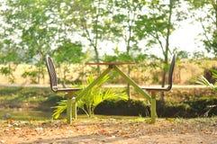 Tabela exterior com as cadeiras no jardim Imagens de Stock
