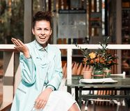 Tabela exterior de assento do café do verão da menina moreno bonita do estilo do moderno Fotografia de Stock