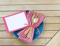 Tabela exterior Placesetting do piquenique do verão com cores brancas e azuis vermelhas com forquilha e colher com um cartão vazi foto de stock