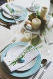 Tabela festiva da Páscoa e da mola decorada em tons azuis e brancos no estilo rústico natural, com ovos, coelho, flores frescas fotos de stock royalty free