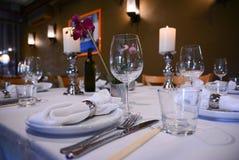 A tabela interior do restaurante ajustou-se com soma, copos da vela em um bem-desenvolvida Foto de Stock