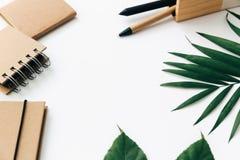 Tabela mínima da mesa de escritório com grupo, fontes e folhas de palmeira dos artigos de papelaria foto de stock royalty free