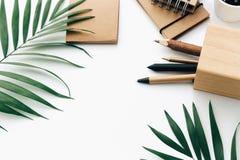 Tabela mínima da mesa de escritório com grupo, fontes e folhas de palmeira dos artigos de papelaria imagem de stock