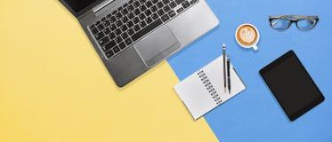 Tabela moderna da mesa de escritório da cor com portátil, caderno, tabuleta e café quente com espaço da cópia fotos de stock