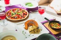 Tabela no restaurante com pratos de vegetariano - pizza, abóbora grelhada, saladas, torta e bebidas imagem de stock