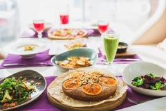 Tabela no restaurante com pratos de vegetariano - pizza, saladas, torta e bebidas fotos de stock royalty free