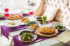 Tabela no restaurante com pratos de vegetariano - pizza, saladas, torta e bebidas naturais frescas foto de stock royalty free