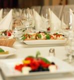 Tabela no restaurante com vidros do alimento e de vinho Fotos de Stock