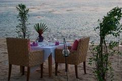 Tabela pequena romântica no litoral, com velas Imagens de Stock