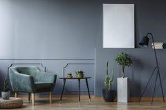 Tabela preta entre a poltrona e plantas verdes no interior cinzento w imagens de stock