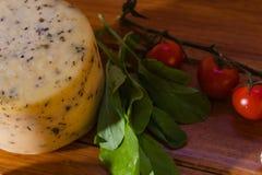 Tabela rústica com um bolo de queijo feito a mão com oréganos imagem de stock royalty free