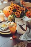 Tabela sazonal tradicional do outono que ajusta-se em casa com abóboras, velas e flores Fotos de Stock Royalty Free