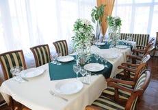 Tabela serida no restaurante Interior brilhante Placas brancas, composições da flor fotos de stock