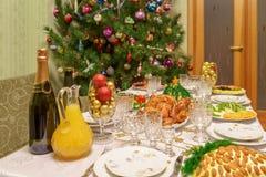 Tabela servida com os pratos festivos perto de Cristo decorado bonito fotos de stock