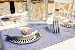 Tabela servida com pratos azuis em uma toalha de mesa branca azul fotos de stock royalty free