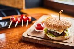 Tabela servida em um café rústico com tomates e hamburguer fotos de stock