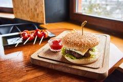 Tabela servida em um café rústico com tomates e hamburguer imagens de stock