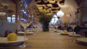 Tabela servida em um restaurante caro Vidros de vinho vazios, placas brancas, cutelaria em uma tabela de madeira Os lim?es sucule filme