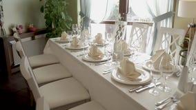 Tabela servida para o banquete em uma sala da luz clara do restaurante pequeno no dia vídeos de arquivo