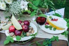 Tabela servida para o jantar com frutos deliciosos e um vidro do vinho tinto fotos de stock