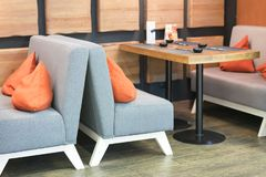 Tabela vazia acolhedor e sofás macios com almofadas em um café imagem de stock royalty free