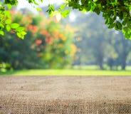 Tabela vazia coberta com o pano de saco sobre árvores borradas com fundo do bokeh Fotografia de Stock Royalty Free