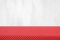 Tabela vazia coberta com a toalha de mesa vermelha do às bolinhas sobre o cem branco Imagens de Stock Royalty Free