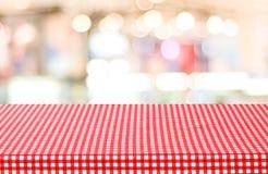 Tabela vazia com toalha de mesa vermelha da verificação sobre o café borrado com bok Imagem de Stock Royalty Free