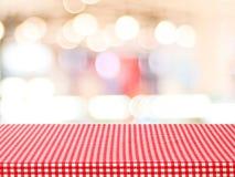 Tabela vazia com toalha de mesa vermelha da verificação sobre o café borrado com bok Foto de Stock