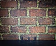 Tabela vazia e fundo escuro do tijolo do vintage Imagens de Stock Royalty Free