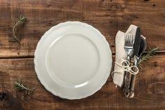 Tabela velha rústica do restaurante com a faca e a colher brancas da forquilha da placa Foto de Stock