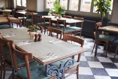 Tabelas colocadas para o serviço no restaurante vazio fotos de stock royalty free