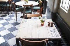 Tabelas colocadas para o serviço no restaurante vazio imagens de stock