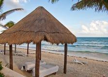 Tabelas da massagem sob a cabana Thatched na praia Fotos de Stock Royalty Free
