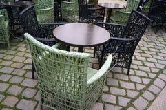 Tabelas de círculo do café e cadeiras de vime no pavimento da rua Imagens de Stock