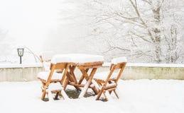 Tabelas de madeira e cadeiras cobertas na neve fresca Fotos de Stock Royalty Free