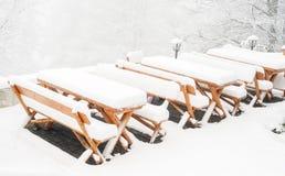 Tabelas de madeira e cadeiras cobertas na neve fresca Imagem de Stock