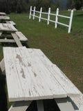 Tabelas de piquenique desvanecidas com a cerca branca no fundo Fotografia de Stock Royalty Free