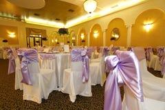 Tabelas do casamento e cadeiras cobertas em um salão de baile Imagens de Stock Royalty Free