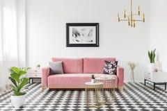 Tabelas do ouro na frente do canapé cor-de-rosa no interior brilhante do apartamento com cartaz e planta Foto real fotos de stock