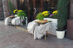 Tabelas e cadeiras com os cafés da rua das coberturas imagem de stock royalty free