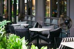 Tabelas e cadeiras de mármore exteriores de acolhimento com os descansos preto e branco acolhedores cercados por plantas verde-cl imagem de stock