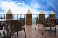 Tabelas e cadeiras de madeira no grande terraço, céu azul fotos de stock royalty free