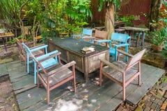 Tabelas e cadeiras de madeira no jardim imagem de stock royalty free
